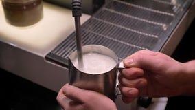 Lanzamiento del primer de las manos del barista que sostienen una jarra de plata con leche de ebullición en ella usando el fregad metrajes