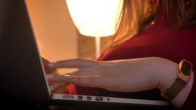 Lanzamiento del primer de las manos femeninas que mecanografían en el ordenador portátil en un apartamento acogedor dentro almacen de metraje de vídeo