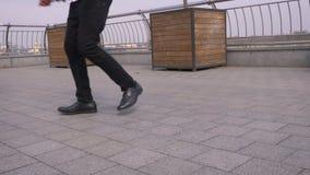 Lanzamiento del primer de las piernas masculinas que hacen un juego de piernas asombroso y que bailan en el aire libre de la call almacen de video