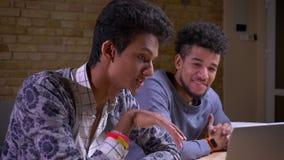 Lanzamiento del primer de los estudiantes masculinos indios y afroamericanos usando los ordenadores portátiles y la discusión de  metrajes
