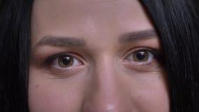 Lanzamiento del primer de los ojos marrones femeninos caucásicos jovenes que miran derecho la cámara con la expresión facial sonr almacen de video