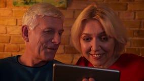 Lanzamiento del primer de los pares felices envejecidos que tienen una llamada video en la tableta que sonríe alegre sentándose e almacen de metraje de vídeo