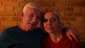 Lanzamiento del primer de los pares felices envejecidos que ven la TV el sonreír con el entusiasmo que se sienta en el sofá dentr almacen de video