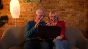 Lanzamiento del primer de los pares felices mayores que tienen una llamada video en el ordenador portátil que se sienta en el sof metrajes