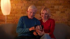 Lanzamiento del primer de los pares felices mayores que tienen una llamada video en el teléfono que se sienta en el sofá dentro e almacen de video