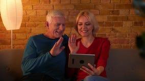 Lanzamiento del primer de los pares felices mayores que tienen una llamada video en la tableta que habla alegre sentarse en el so metrajes