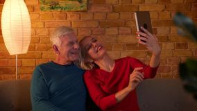Lanzamiento del primer de los pares felices mayores que toman selfies en la tableta que se sienta en el sofá dentro en un apartam almacen de video