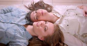 Lanzamiento del primer de los pares lesbianos hermosos jovenes que sonríen y que ríen feliz la colocación en el piso en comprado  almacen de video