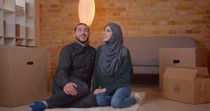 Lanzamiento del primer de los pares musulmanes alegres jovenes que se sientan en el piso al lado de las cajas en una sonrisa nuev almacen de video