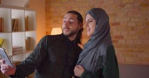 Lanzamiento del primer de los pares musulmanes alegres jovenes que tienen una llamada video en la tableta y que muestran apagado  metrajes