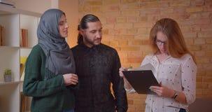 Lanzamiento del primer de los pares musulmanes felices jovenes que discuten con un realter un nuevo apartamento que sonríe alegre almacen de metraje de vídeo