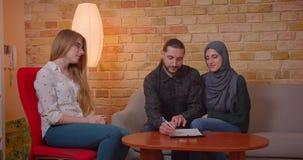 Lanzamiento del primer de los pares musulmanes felices jovenes que discuten con un realter un nuevo apartamento que sonr?e alegre almacen de metraje de vídeo