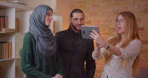Lanzamiento del primer de los pares musulmanes felices jovenes que hablan con el realter con una tableta en un abrazo nuevamente  almacen de video