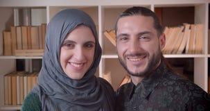 Lanzamiento del primer de los pares musulmanes felices jovenes que miran derecho la cámara y que sonríen y que abrazan alegre en  metrajes