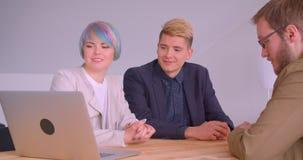 Lanzamiento del primer de los socios comerciales mujer y hombres que tienen una reunión de almuerzo usando el ordenador portátil  almacen de metraje de vídeo