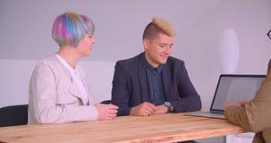 Lanzamiento del primer de los socios comerciales mujer y hombres que tienen una reunión usando el ordenador portátil en el café d almacen de metraje de vídeo