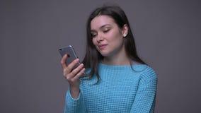 Lanzamiento del primer de mandar un SMS femenino moreno bonito joven en el teléfono con el fondo aislado en gris almacen de metraje de vídeo
