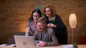 Lanzamiento del primer de tres colegas amistosos que tienen una llamada video en el ordenador portátil que ríe y que se divierte  almacen de metraje de vídeo