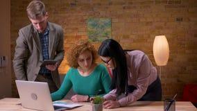 Lanzamiento del primer de tres empleados que discuten los datos usando la tableta y los gráficos del ordenador portátil que discu almacen de video