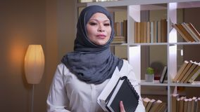 Lanzamiento del primer del doctor de sexo femenino musulmán adulto en el hijab que sostiene los libros y que mira derecho la cáma almacen de metraje de vídeo