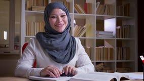 Lanzamiento del primer del doctor de sexo femenino musulmán adulto en hijab que estudia para un examen médico que mira la cámara  metrajes