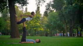 Lanzamiento del primer del ejercicio de fabricación femenino delgado joven de la yoga en el parque que es aumentado para arriba m almacen de video