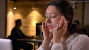 Lanzamiento del primer del empleado de sexo femenino bonito joven que tiene un dolor de cabeza mientras que mecanografía en el or fotos de archivo libres de regalías