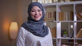 Lanzamiento del primer del empleado de sexo femenino musulmán adulto en hijab que estudia el gráfico en la biblioteca que está pe metrajes