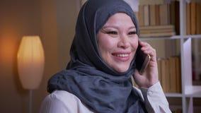 Lanzamiento del primer del empleado de sexo femenino musulmán adulto en hijab que habla feliz en el teléfono en la biblioteca en  almacen de video