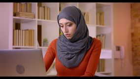 Lanzamiento del primer del empleado de sexo femenino musulmán atractivo joven que mecanografía en el ordenador portátil y que son almacen de metraje de vídeo