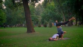 Lanzamiento del primer del entrenamiento masculino y femenino un ejercicio del acroyoga en el parque al aire libre Hombre que es  metrajes