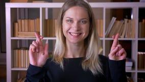 Lanzamiento del primer del estudiante atractivo joven que hace sus fingeres cruzar con la esperanza que mira la c?mara dentro en almacen de metraje de vídeo