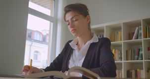 Lanzamiento del primer del estudiante caucásico bonito joven que toma notas en la biblioteca de universidad almacen de metraje de vídeo