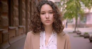 Lanzamiento del primer del estudiante caucásico rizado de pelo largo joven que sonríe feliz caminando hacia cámara al aire libre  almacen de metraje de vídeo
