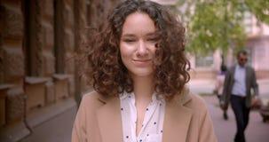 Lanzamiento del primer del estudiante caucásico rizado de pelo largo joven que sonríe feliz caminando hacia cámara al aire libre  almacen de video
