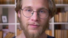 Lanzamiento del primer del estudiante masculino atractivo adulto en los vidrios que cabecean la sonrisa alegre mirando la cámara  almacen de metraje de vídeo