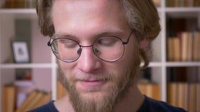 Lanzamiento del primer del estudiante masculino atractivo adulto en vidrios que sonríe alegre mirando la cámara en la biblioteca  almacen de metraje de vídeo