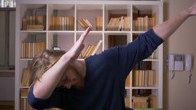Lanzamiento del primer del estudiante masculino atractivo adulto que frota con confianza y que mira la cámara en la biblioteca de almacen de metraje de vídeo