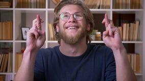 Lanzamiento del primer del estudiante masculino atractivo adulto que hace sus fingeres cruzar y que mira la cámara en la universi almacen de metraje de vídeo