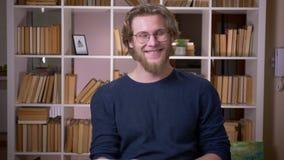 Lanzamiento del primer del estudiante masculino atractivo adulto que lee un libro y que mira la cámara que sonríe feliz en la uni almacen de video