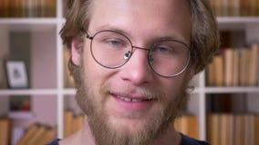 Lanzamiento del primer del estudiante masculino cauc?sico atractivo adulto en vidrios que sonr?e alegre mirando la c?mara en almacen de metraje de vídeo