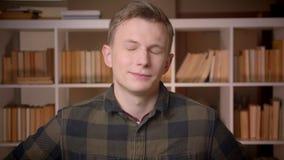 Lanzamiento del primer del estudiante masculino caucásico atractivo joven que cabecea diciendo sí la sonrisa alegre mirando la cá almacen de video