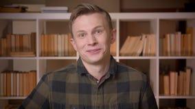 Lanzamiento del primer del estudiante masculino caucásico atractivo joven que es excitado y de la risa sorprendida mirando la cám almacen de metraje de vídeo