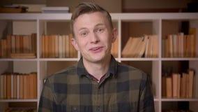Lanzamiento del primer del estudiante masculino caucásico atractivo joven que es excitado y sorprendido mirando la cámara en la u almacen de metraje de vídeo