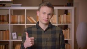 Lanzamiento del primer del estudiante masculino caucásico atractivo joven que muestra un pulgar encima de mirar la cámara en la b almacen de metraje de vídeo