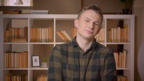 Lanzamiento del primer del estudiante masculino caucásico atractivo joven que sonríe feliz mirando la cámara en la biblioteca de  almacen de metraje de vídeo