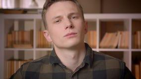 Lanzamiento del primer del estudiante masculino caucásico confiado joven que mira la cámara en la biblioteca de universidad almacen de video