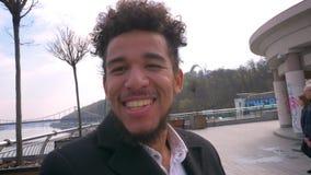 Lanzamiento del primer del hombre afroamericano atractivo joven que tiene una llamada video que agita hola y que sonríe a la cáma metrajes