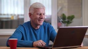 Lanzamiento del primer del hombre caucásico envejecido que tiene una llamada video en el ordenador portátil que sonríe feliz dent almacen de video