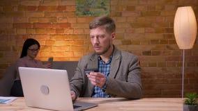 Lanzamiento del primer del hombre de negocios adulto que hace compras en línea en el ordenador portátil con la tarjeta de crédito almacen de metraje de vídeo